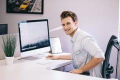 Молодой работник сидя в офисе на компьютере Фрилансер в белой рубашке Дизайнер сидит перед окном внутри стоковые фото