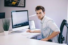 Молодой работник сидя в офисе на компьютере Фрилансер в белой рубашке Дизайнер сидит перед окном внутри стоковые фотографии rf