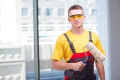 Молодой рабочий-строитель в желтых coveralls Стоковое Изображение RF