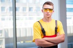 Молодой рабочий-строитель в желтых coveralls Стоковые Фотографии RF