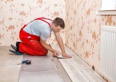 Молодой разнорабочий устанавливая деревянный пол стоковая фотография