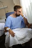 Молодой раненый человек плача в палате сидя самостоятельно плакать в боли потревожился для его состояния здоровья Стоковое Изображение RF