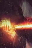 Молодой ратник держа саблю в огне стоковое изображение rf