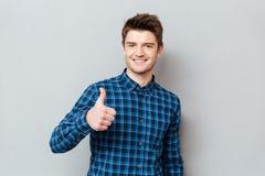 Молодой радостный человек студента держа большой палец руки вверх стоковые изображения