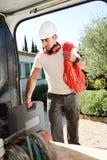 Молодой ремесленник электрика принимая инструменты из профессионального фургона тележки Стоковые Изображения RF
