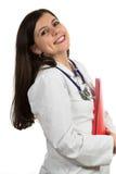 Молодой дружелюбный красивый женский доктор держа папку и усмехаться Стоковое Изображение RF