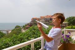Молодой самолет бумаги владением мальчика, наслаждается летним днем на голубом море Стоковое Изображение