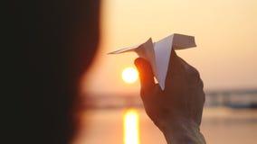 Молодой самолет бумаги старта парня против моря во время захода солнца с пирофакелом солнца и отражений в воде, как в детстве Стоковые Изображения RF