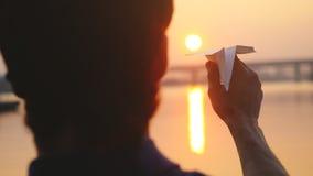 Молодой самолет бумаги старта парня против моря во время захода солнца с пирофакелом солнца и отражений в воде, как в детстве Стоковое фото RF