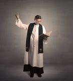 Молодой священник в давать его благословение Стоковые Фото