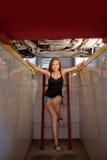 Молодой сексуальный механик брюнет в проверенной рубашке в яме ремонта автомобиля Стоковые Изображения