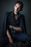 Молодой сексуальный человек в классическом костюме сидя на стуле стоковые фотографии rf