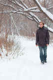 Молодой серьезный человек в джинсах идет в лес на зиме Стоковая Фотография RF