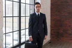 Молодой серьезный человек стоя близко окно офиса Работодатель предпринимателя босса директора менеджера Стоковые Изображения RF