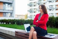 Молодой сердитый профессиональный сидеть бизнес-леди внешний с рукой Стоковое Изображение RF