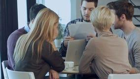 Молодой сердитый человек обсуждая изучение рыночной конъюнктуры с коллегами в встрече сток-видео