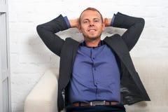 Молодой сидеть бизнесмена ослабил с руками за его головой, мечтать, думать или отдыхать Стоковое Изображение RF
