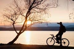 Молодой силуэт велосипедиста на предпосылке голубого неба и захода солнца на пляже Конец сезона на озере Стоковая Фотография
