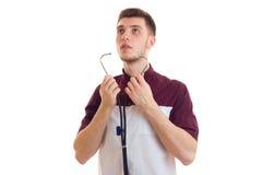 Молодой сильный доктор лаборатории смотрит вверх и кладет стетоскоп в ваши уши изолирован на белой предпосылке Стоковая Фотография RF