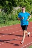Молодой спортсмен бежать на следе Стоковые Изображения RF