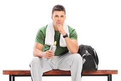 Молодой спортсмен держа бутылку с водой усаженный на стенд Стоковая Фотография RF