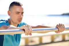 Молодой спортсмен делая уклон нажим-поднимает стоковая фотография