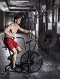 Молодой спортсмен используя велотренажер на спортзале Стоковое фото RF