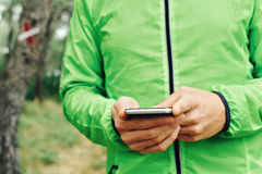 Молодой спортсмен используя его smartphone стоковые изображения rf
