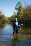 Молодой спортсмен пересекая скалистую местность с велосипедом в его руках Стоковые Изображения