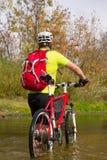 Молодой спортсмен пересекая скалистую местность с велосипедом в его руках Стоковые Фото
