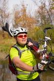 Молодой спортсмен пересекая скалистую местность с велосипедом в его руках Стоковое Изображение