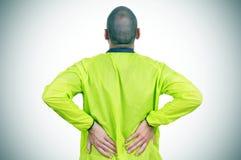 Молодой спортсмен с болью внизу спины стоковая фотография