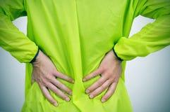 Молодой спортсмен с болью внизу спины стоковое изображение