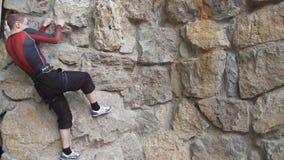 Молодой спортсмен с специальным оборудованием взбирается на стене парень взбирается стеной утеса во время конкуренции скалолазани сток-видео