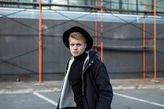 Молодой стильный человек в ультрамодной носке смотрит отсутствующим пока стоящ outdoors Стиль улицы Стоковое Фото