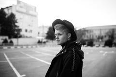Молодой стильный человек в ультрамодной носке смотрит отсутствующим пока стоящ outdoors Стиль улицы Стоковое Изображение RF