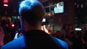 Молодой стильный человек поет в клубе для людей Партия в ночном клубе Stendap шуточное на этапе говорит шутку Мюзикл видеоматериал