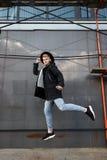 Молодой стильный человек redhead в ультрамодном обмундировании имеет потеху и скакать против городской стены outdoors Стоковые Фотографии RF