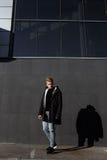 Молодой стильный человек redhead в ультрамодном обмундировании представляя против городской предпосылки Стоковые Фотографии RF