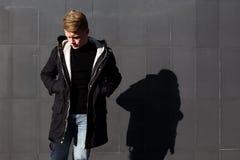 Молодой стильный человек redhead в ультрамодном обмундировании представляя против городской предпосылки Стоковые Фото