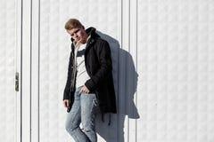 Молодой стильный человек redhead в ультрамодном обмундировании представляя против городской предпосылки Стоковое Изображение