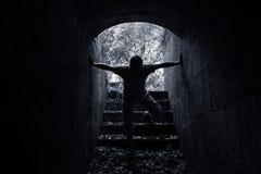 Молодой страшный человек входит в темный каменный тоннель Стоковое Фото