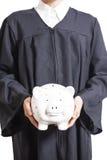 Молодой студент-выпускник в мантии держа копилку Стоковое Фото