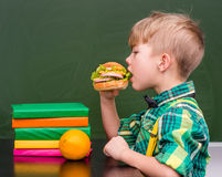 Молодой студент есть сандвич на обеденном времени Стоковая Фотография