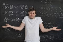 Молодой студент делает экзамен математики и не умеет как разрешить трудную математически проблему стоковая фотография