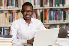 Молодой студент используя его компьтер-книжку в библиотеке Стоковая Фотография