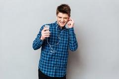 Молодой студент наслаждаясь музыкой в наушниках на smartphone стоковые изображения rf