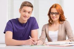 Молодой студент подготавливая к экзаменам и усмехаться Стоковое Фото