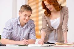 Молодой студент подготавливая к экзаменам и усмехаться Стоковое фото RF