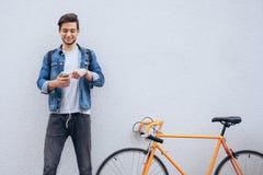 Молодой студент стоя около велосипеда смотря телефон и слушая к музыке Стоковая Фотография RF